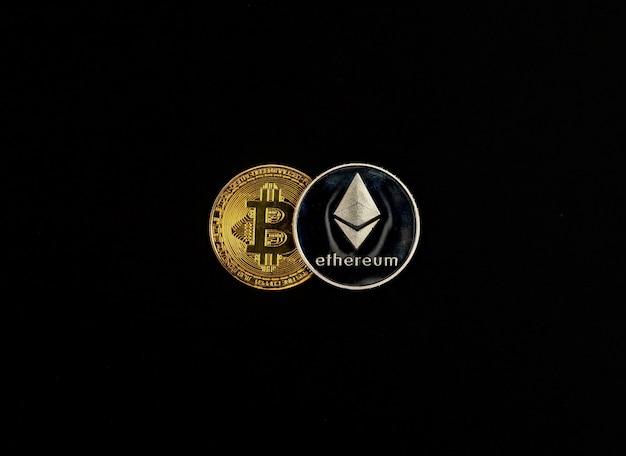 黒の背景に光沢のある金色のビットコイン上のイーサリアム銀貨。暗号通貨の概念の交換。
