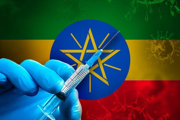 에티오피아 covid19 예방 접종 캠페인 파란색 고무 장갑을 끼고 깃발 앞에 주사기를 들고 있습니다.