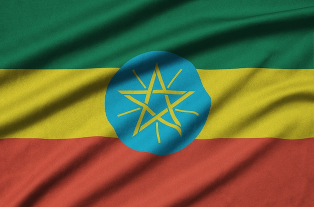 Ethiopia flag is depicted on a sports cloth fabric with many folds.