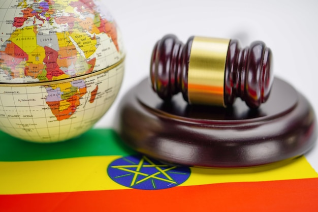 Ethiopia flag and judge hammer with globe world map