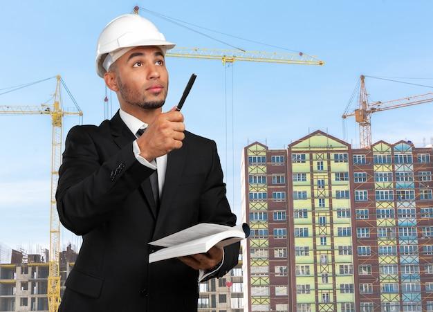 Ethnic architect holding blueprints