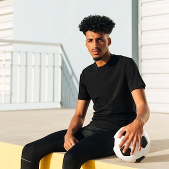 Ethnic athletic guy sitting with soccer ball