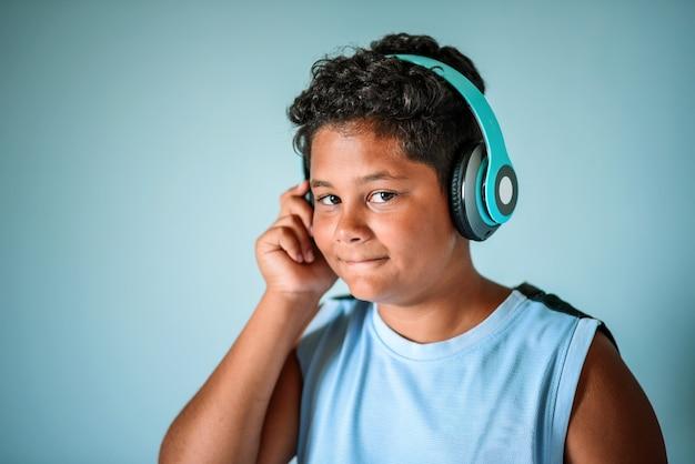 Этнический мальчик слушает музыку в наушниках