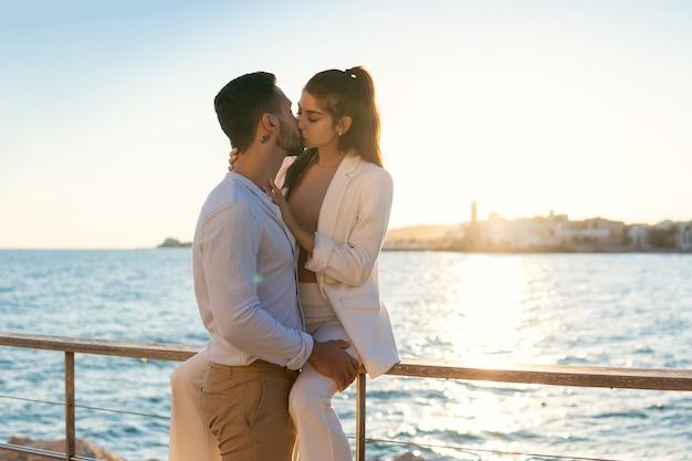 Этническая влюбленная пара, целующаяся на набережной моря