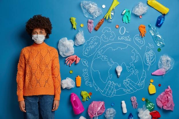 민족적인 곱슬 머리 여자는 니트 오렌지 점퍼와 데님 바지를 입은 보호용 안면 마스크를 착용하고 불행하게 보이며 대기 오염과 심각한 오염 문제로 인해 방해 받고 있습니다.