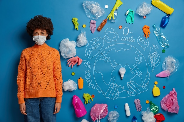 Ethnic curly woman wears protective face mask, dressed in knitted orange jumper and denim pants, looks unhappily, being disturbed by air pollution and serious problem of contamination