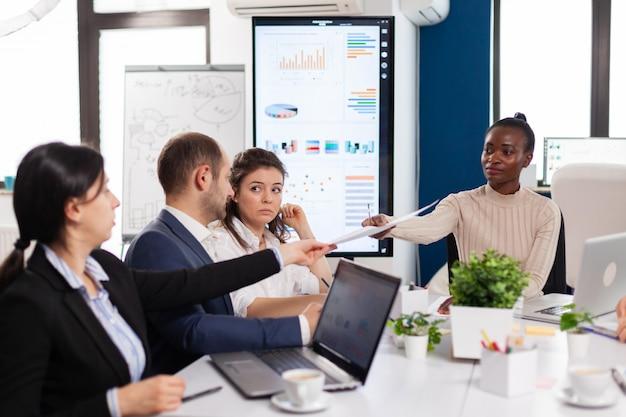 会議室の会議に座っているエスニックエグゼクティブマネジメントプランニングビジネスプラン