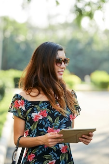 Ethnic female with tablet looking away