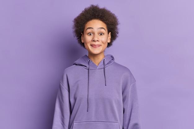 Ragazza etnica con i capelli afro sorride piacevolmente e guarda curiosamente indossa una felpa con cappuccio.