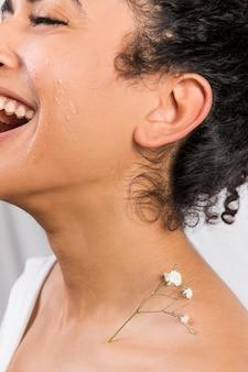 Ethnic happy woman with plant on neck