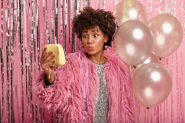 La bella femmina etnica fa selfie, ha le labbra piegate, posa vicino a mongolfiere, indossa abiti scintillanti e cappotto alla moda, si gode la vita notturna, celebra la festa con gli amici.