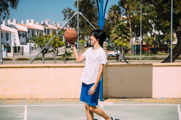 Ethnic male holding basketball while standing on playground