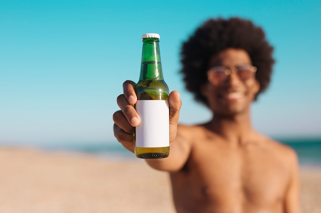 Ethnic man holding bottle of beer
