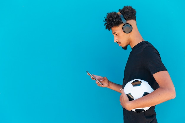 Ethnic player with football using phone and headphones