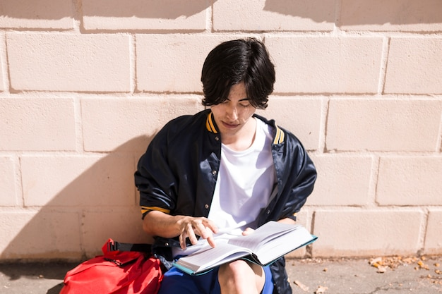 Ethnic pupil sitting on asphalt with open book