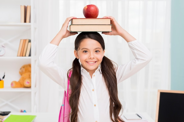 Ethnic schoolgirl holding books on head