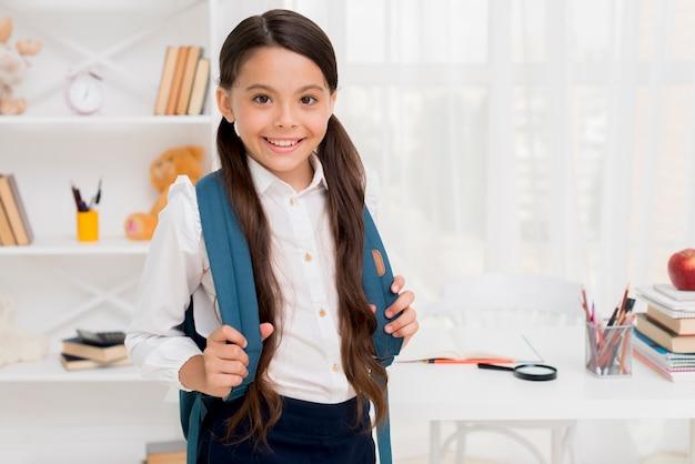 Ethnic schoolgirl holding straps of knapsack