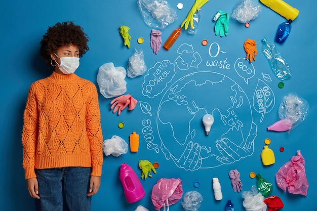 Ethnic serious woman wears medical face on face, breathes polluted air, turns away looks at plastic trash, drawn planet, dressed in orange jumper, has health danger because of contamination.