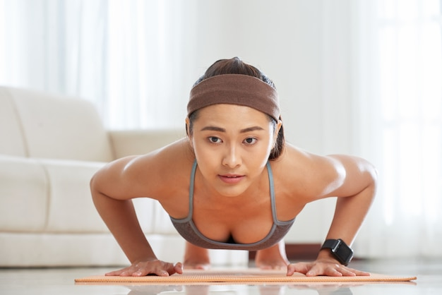 Ethnic sportswoman training on mat