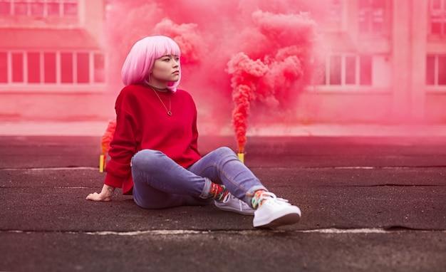 Этнический подросток смотрит в сторону возле розовой дымовой шашки