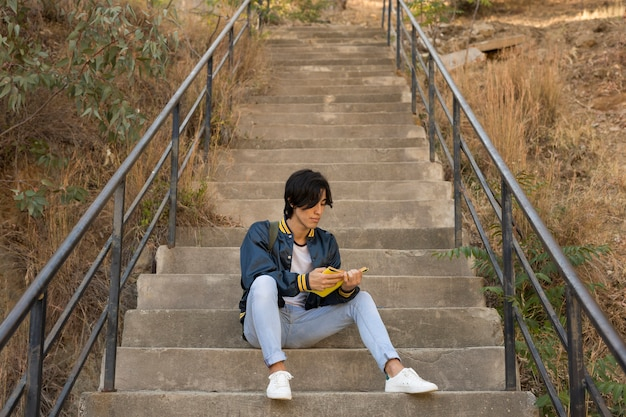 Ethnic teenager sitting with book on stairs