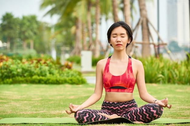 Ethnic woman meditating on green lawn