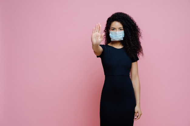 Ethnic woman with curly hair makes stop gesture with palm, says no to coronavirus
