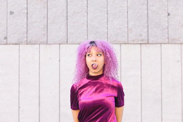 Этническая женщина с фиолетовыми волосами дует розовая жвачка