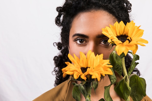 Ethnic woman with yellow flowers near face