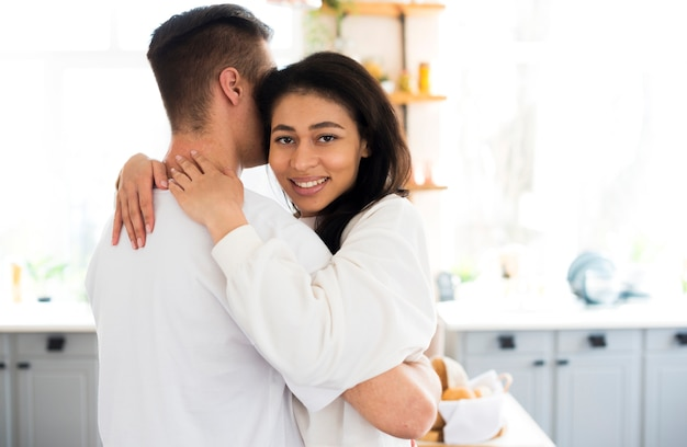 Ethnic young female hugging boyfriend and looking at camera