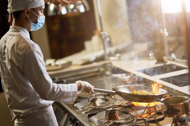 불타는 팬에 볶음을 만드는 열성적인 젊은 요리사