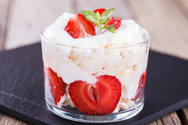 Eton mess - strawberries with whipped cream and meringue in a glass beaker