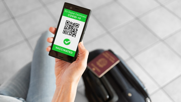 Eu digital certificate app for smartphone with vaccinated sign and quad code