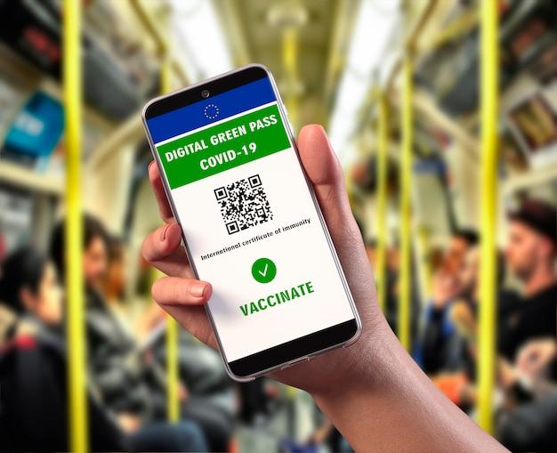 Цифровой зеленый пропуск ес с qr-кодом на экране мобильного телефона, фоновый интерьер вагона метро. covid-19 иммунитет. путешествуйте без ограничений