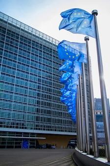 Флаг ес развевается перед зданием европейского парламента в брюсселе, бельгия