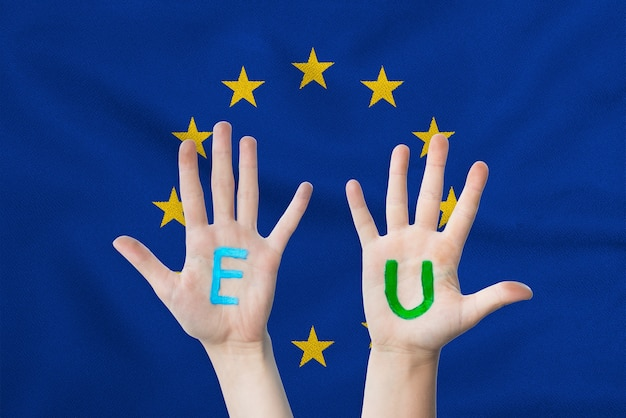 Eu inscription on the children's hands against the surface of a waving flag of the european union.