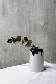Ветка эвкалипта в керамической вазе на белой льняной скатерти с серой стеной позади