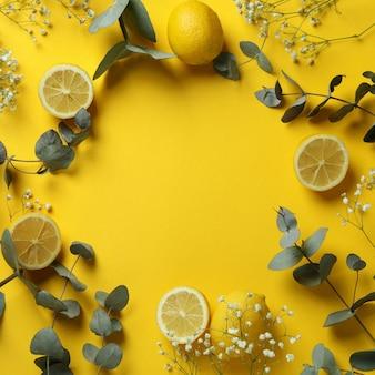 Ветви эвкалипта, лимоны и гипсофила на желтом фоне
