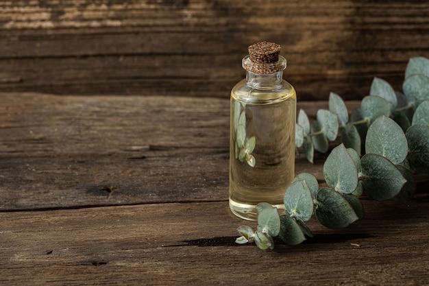 Эфирное масло эвкалипта и свежие листья эвкалипта на деревянном фоне. естественная концепция.