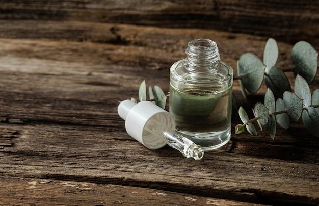Эфирное масло эвкалипта и свежие листья эвкалипта на дереве