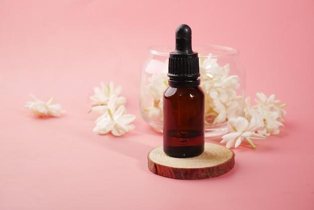 유리 병에 유칼립투스 에센셜 오일과 분홍색 배경에 꽃