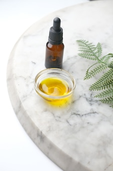 타일에 녹색 잎이있는 유리 병에 유칼립투스 에센셜 오일