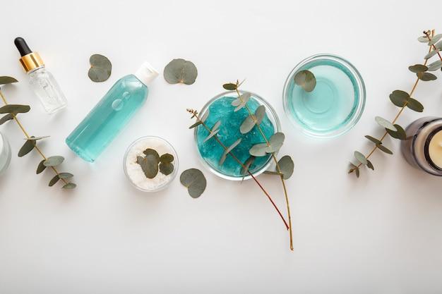 ユーカリ植物の葉と枝が入ったボトルに入ったユーカリジェルセラムナチュラルコスメティックス。スキンケア化粧品に含まれるユーカリハーブオイル、代替医療アロマセラピーホワイトバクグラウンド。