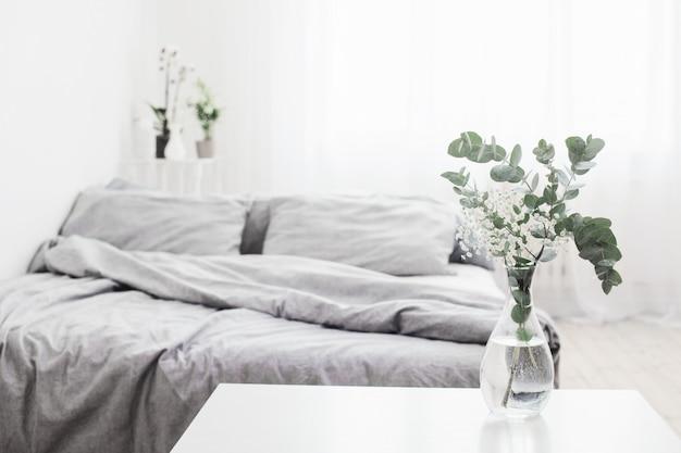 白い寝室のガラス花瓶のユーカリ