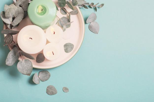 ユーカリの葉と青色の背景に非常に熱い蝋燭