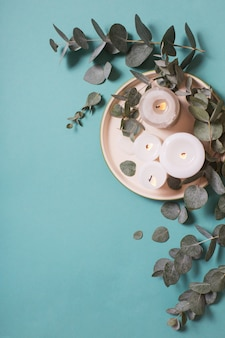 Eucalyptus leaves and burning candles on blue background