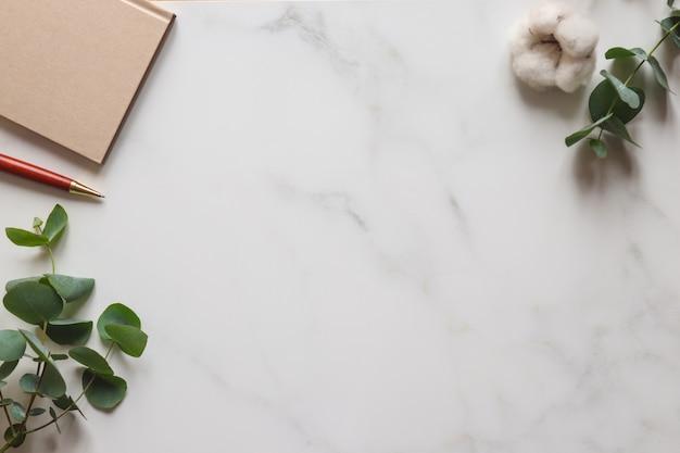 ユーカリの葉は、コピースペースのある白い大理石のテーブルに、綿の花のメモ帳とペンを残します