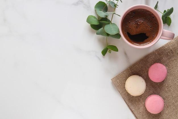 コピースペースのある白い大理石のテーブルに、ユーカリの葉、一杯のコーヒー、ピンクのマカロン