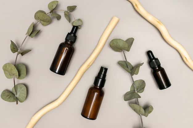 Eucalyptus oil in dark glass dropper bottle with herbal extract, skin care and alternative medicine concept, eucalyptus leaves on the background.