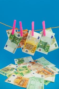 Деньги euero на веревке прищепка на синем фоне
